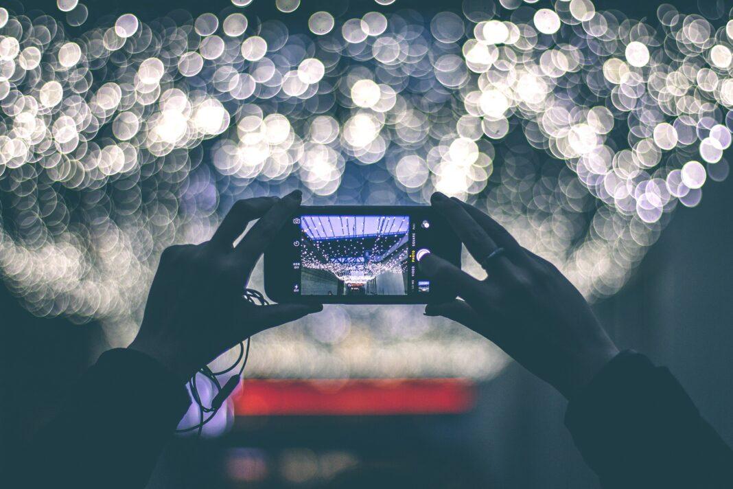 Ein Smartphone beim Fotografieren mit zwei Händen.